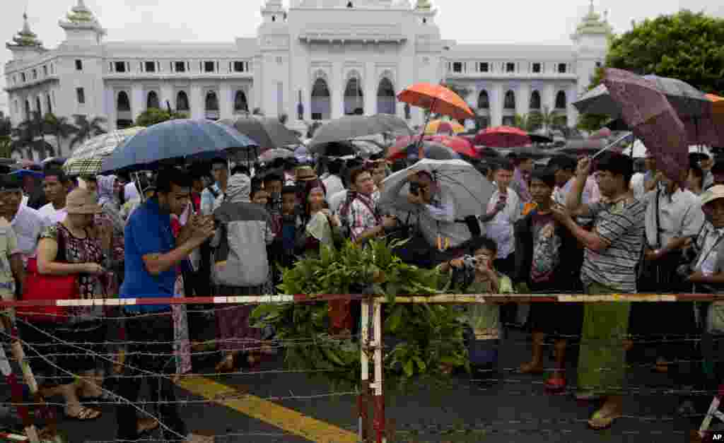 People gather to take pictures of a wreath of flowers on a barbed-wired roadside barrier outside Rangoon City Hall commemorating the victims of August 8, 1988 pro-democracy uprising, Rangoon, August 8, 2013.