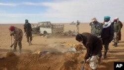 Abakorerabushake hamwe n'abategetsi bariko barapfuba ibisigarira vy'abimukira bapfiriye mu bugaragwa bwa Sahara, Niger, itariki 30/10/2013.