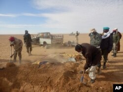 FILE - Volunteers and officials dig graves to inter the bodies of migrants who died of thirst after their the truck they were traveling in, seen rear, broke down while attempting to cross the Sahara Desert north of Arlit, Niger, Oct. 30, 2013.