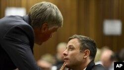Oscar Pistorius parle avec un de ses avocats au tribunal de Pretoria, Afrique du Sud, 21 octobre 2014