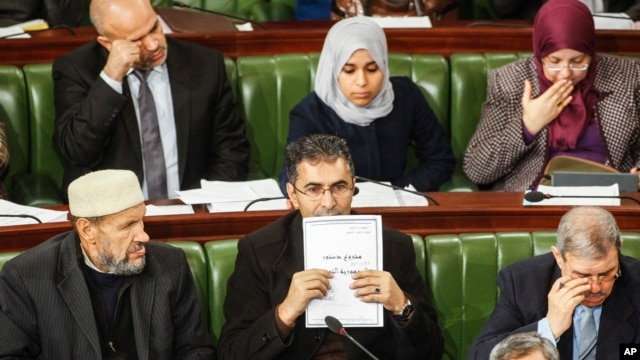 "A member of Tunisia's parliament holds up a copy of a document that reads in Arabic ""Draft Constitution of the Republic of Tunisia,""Jan. 3, 2014 in Tunis."