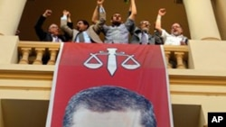Egyptian campaign officials of the Muslim Brotherhood's candidate, Mohammed Morsi, celebrate over a giant poster of him at his campaign headquarters in Cairo, Egypt, Sunday, June 24, 2012.