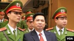 Polisi Vietnam mengawal Cu Huy Ha Vu keluar dari ruang persidangan di pengadilan Hanoi, Senin (4/4).