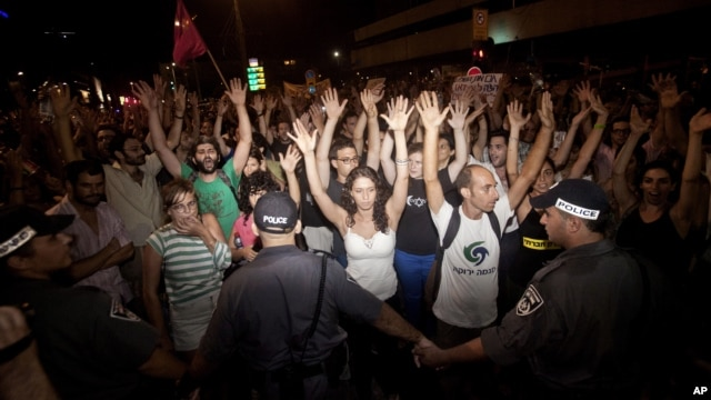 Israeli activists raise their hands during a social protest in Tel Aviv, June 24, 2012.