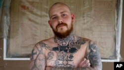 Shane Johnson displays some of his tattoos as he poses in his home in Tippecanoe, Indiana, Jan. 12, 2017. Johnson who was born into extremism is in the process of covering some of his racist tattoos with new ones and wears long sleeves to hide remnants of the past he regrets. His father and many of his father's relatives were part of the Klan, he said, so there was only one real way for him to go as a youth.