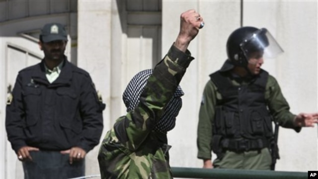 A demonstrator chants slogans in front of the Bahraini Embassy in Tehran, Iran as he covers his face in the style of Palestinian militants, in a protest against Saudi and Bahraini leaders to condemn the crackdown on the Bahraini opposition, April 15, 2011