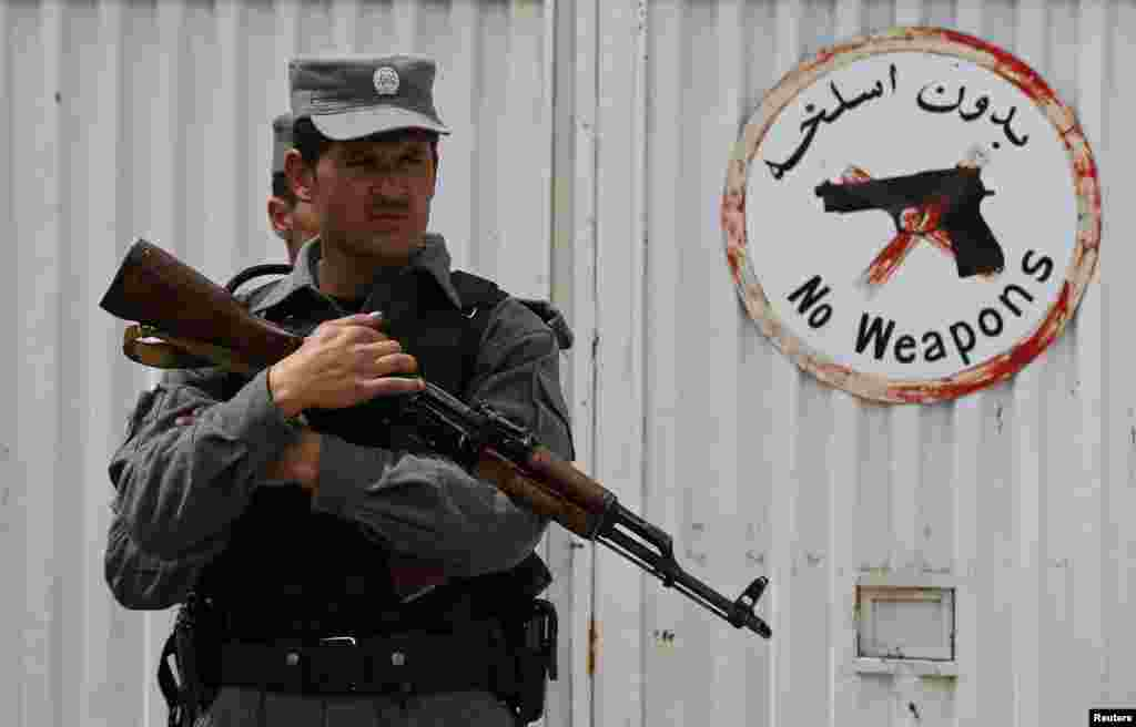 An Afghan police officer stands at the gate of Cure Hospital after three Americans were killed, Kabul, April 24, 2014.