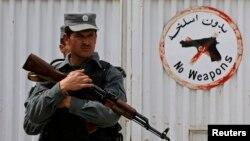 Cảnh sát Afghanistan canh gác trước cổng Bệnh viện Cure sau vụ nổ súng khiến 3 người Mỹ thiệt mạng.