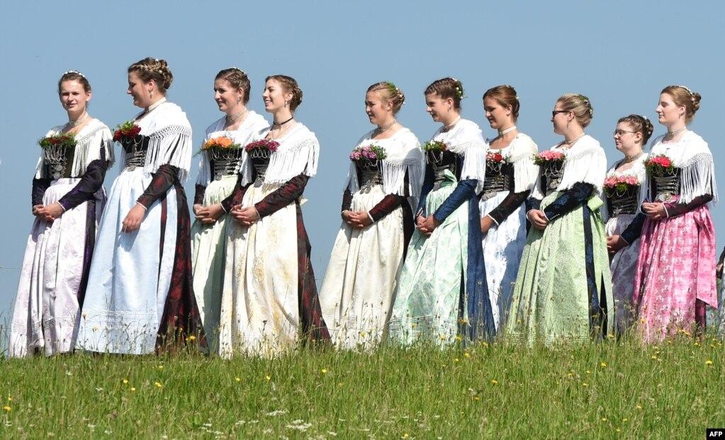 Para perempuan berpakaian tradisional Bavaria ambil bagian dalam prosesi Corpus Christi di desa Wackersberg, Jerman.