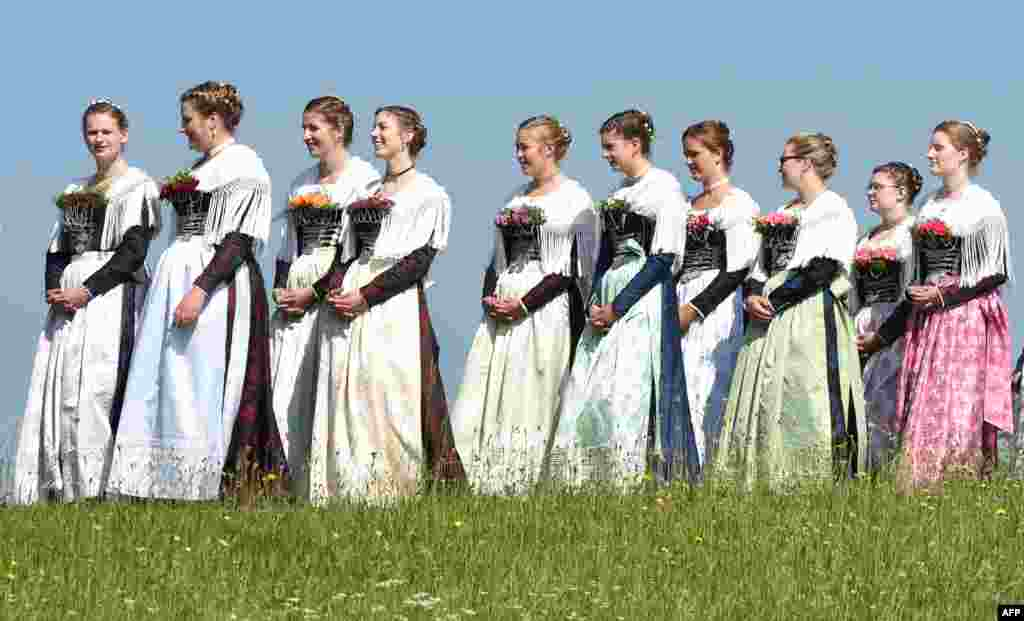 Women dressed in Bavarian clothes take part in the traditional Corpus Christi procession near the village of Wackersberg, Germany.