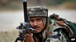 An Indian Army soldier takes position during an encounter with armed suspected militants at Pindi Khattar village in Arnia border sector, 43 kilometers (27 miles) south of Jammu, India, Nov. 27, 2014.