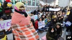 """在韩国首尔日本大使馆前的一次集会上,学生们聚集在一个""""慰安妇""""雕像附近。 (2017年1月11日美联社资料照)"""