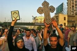 Une musulmane lève le Coran, le livre saint de l'Islam, dans un geste de solidarité avec les Coptes victimes de violence au Caire (10 octobre 2011)