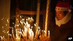 Seorang anggota jemaat menyalakan lilin di Gereja Nativity di Bethlehem, Tepi Barat (24/12). (AP/Majdi Mohammed)