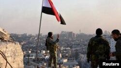 ທະຫານລັດຖະບານຊີເຣຍ ຄົນໜຶ່ງ ຍົກນິວມື ສັນຍາລັກ ເປັນໂຕ V ຢູ່ກ້ອງທຸງຊາດຂອງຊີເຣຍ ໃນຂະນະທີ່ແນມອອກໄປທາງພາກຕາເວັນອອກ ຂອງເມືອງ ອາເລັບໂປ ຫຼັງຈາກທີ່ກອງທະຫານ ໄດ້ເຂົ້າຄວບຄຸມ ຄຸ້ມ al-Sakhour ໃນເມືອງ Aleppo, ຂອງຊີເຣຍ,ໃນພາບໃບປິວ ສະໜອງໂດຍ ອົງການຂ່າວ SANA ຂອງທາງການ, ວັນທີ 28 ພະຈິກ 2016.