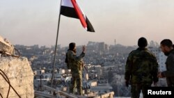Under the Syrian flag, a government soldier makes a V sign while overlooking eastern Aleppo, after troops took control of the city's al-Sakhour neigborhood, in this photo provided by SANA, the state-run news agency, Nov. 28, 2016.