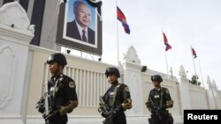 Cambodian government security forces walk in front of the Council of Ministers building as they patrol along a street ahead of the 21st ASEAN Summit and other related summits in Phnom Penh, November 13, 2012.