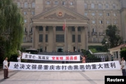 FILE - Residents hold banners outside the high court where Wen Qiang, the former municipal justice chief, was sentenced to death in Chongqing municipality. Simplified characters such as these were introduced in the mainland as part of a literacy campaign.