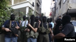 Shi'ite masked gunmen from the Meqdad clan, gather at the Meqdad family's association headquarters in the southern suburbs in Beirut, Lebanon, August 15, 2012.