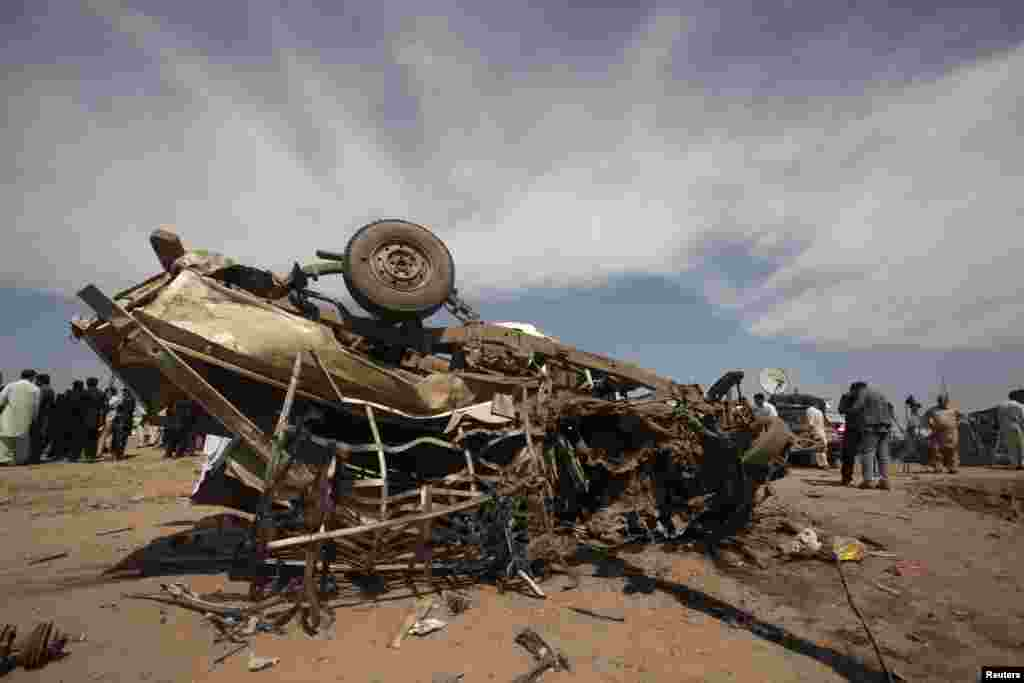 An overturned car is seen at the site of a bomb attack in Jalozai camp in Nowshera district, northwestern Pakistan, March 21, 2013.