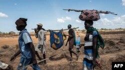 Des proches accompagnent une femme dinka touchée par le choléra dans un hôpital temporaire à Mingkaman, un camp pour personnes déplacées internes (PDI), dans les États des Lacs de l'Est, Soudan du Sud, 26 avril 2017.