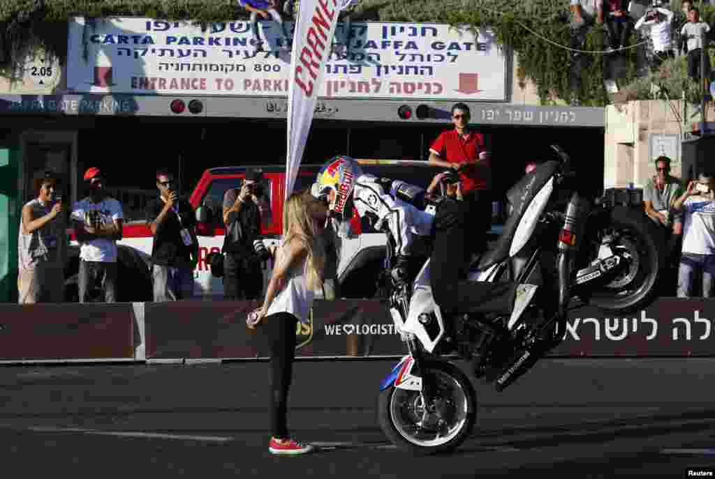 Stunt rider Chris Pfeiffer performs on his BMW motorcycle during an road show in Jerusalem.