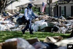 FILE - Postal worker Lonzell Rector makes his rounds among flood-damaged debris from homes that lines the street in the aftermath of Hurricane Harvey in Houston, Sept. 7, 2017.