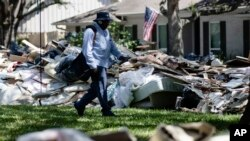 Postal worker Lonzell Rector makes his rounds among flood-damaged debris from homes that lines the street in the aftermath of Hurricane Harvey in Houston, Sept. 7, 2017.