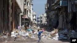 Humus'ta enkazların arasında hala oyun oynamaya çalışan bir çocuk