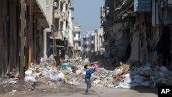 ក្មេងប្រុសស៊ីរីម្នាក់លេងនៅចន្លោះអគារបែកបាក់នៅក្នុងក្រុង Homs ប្រទេសស៊ីរី កាលពីថ្ងៃទី២៦ ខែកុម្ភៈ ២០១៦។