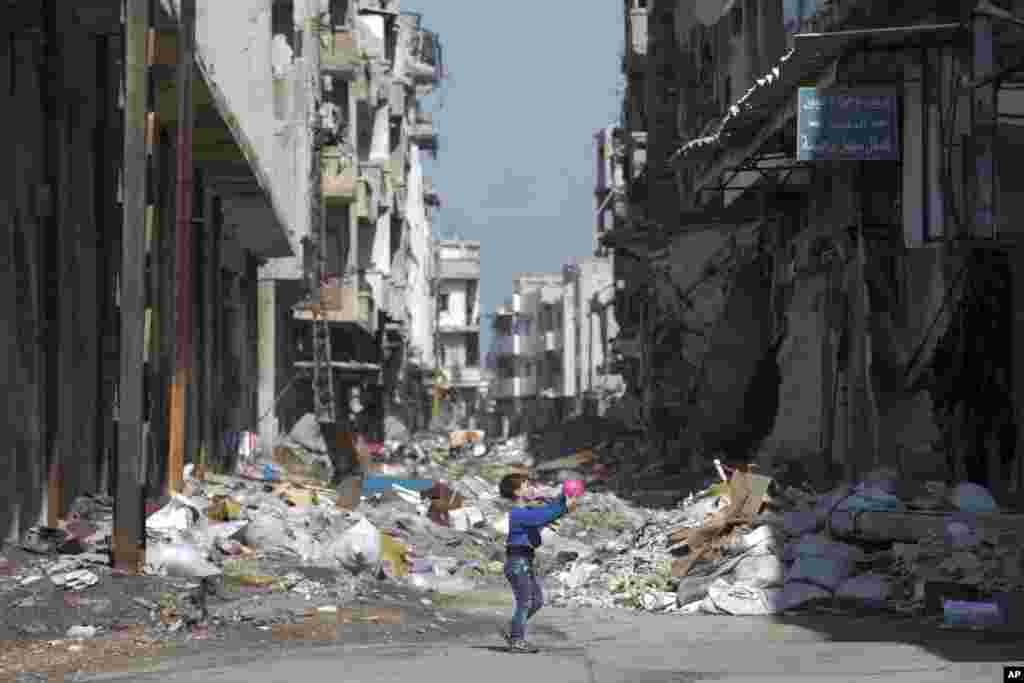 "A Syrian boy plays between destroyed buildings in the old city of Homs, Syria. The U.N. Security Council is expected to vote Friday afternoon on a draft resolution endorsing the ""cessation of hostilities"" in Syria that is set to start at midnight local time."
