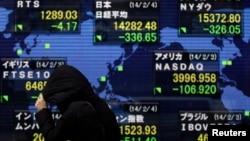 4일 일본 닛케이 지수가 3 달 만에 최저치를 기록한 가운데, 한 행인이 증권거래소 전광판 앞을 지나가고 있다.