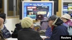 Dân chúng xem tin tức truyền hình khi sơ tán đến một trường học trên khu đất cao, sau khi cảnh báo sóng thần được đưa ra