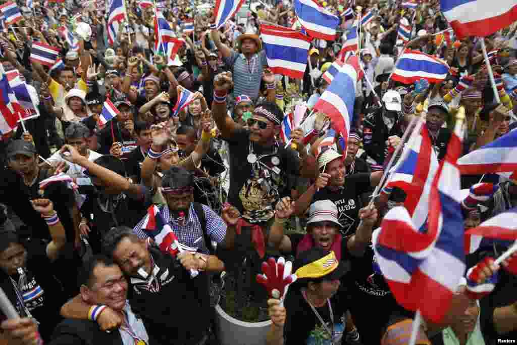 wapinzani wa serikali wakipeperusha bendera na kupiga firimbi wakati kiongozi moja wa upinzani kuwahutubia mbele ya wizara ya fedha katika kuipinga serikali Bangkok, Nov. 26, 2013.
