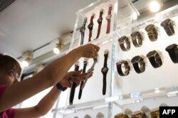 """Seorang pramuniaga membetulkan letak jam tangan di pajangan salah satu gerai jam tangan """"Swatch"""" di Beijing, China, 29 Agustus 2015. (Foto: dok)."""
