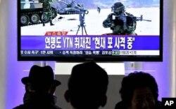 سێ هاوڵاتی کۆریای باشور له شوێـنێـکی گشـتی سهیری مهشق و ڕاهێنانی لهشـکری وڵاتهکهیان دهکهن، دووشهممه 20 ی دوازدهی 2010