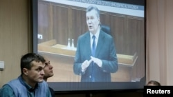 Viktor Yanukovych gives evidence via a video link seen on a courtroom screen in Kyiv, Ukraine, Monday, Nov. 28, 2016. The former president testified during the trial of former police officers suspected of killing protesters during the Maidan street revolt in 2014.