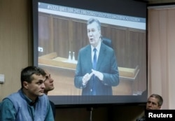 FILE - Former Ukrainian pesident Viktor Yanukovych testifies via a video link from Russia on a courtroom screen in Kyiv, Ukraine, Nov. 28, 2016. Widely considered corrupt and a crony of Russian President Vladimir Putin, he was ousted in a popular uprising that culminated with Yanukovych fleeing Ukraine for Russia in February of 2014.