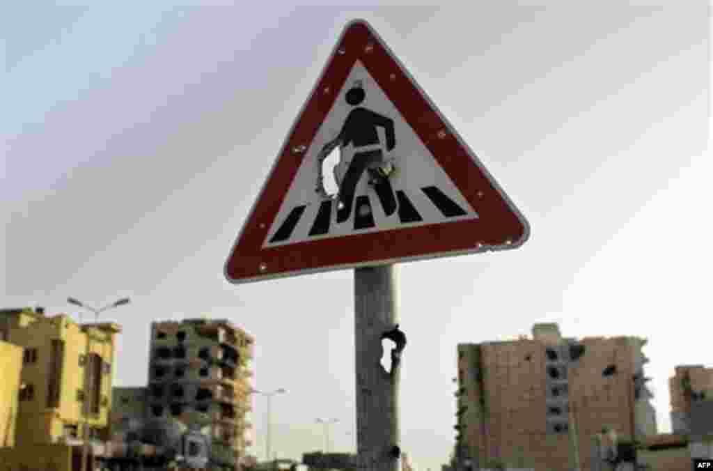 A foot crossing road sign with holes seen at Tripoli street in Misrata, Libya, Friday, Sept. 2, 2011. (AP Photo/Sergey Ponomarev)