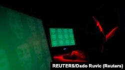 Seorang pria berpose di depan layar yang menunjukkan kata 'cyber' dalam kode biner, dalam ilustrasi gambar ini diambil di Zenica 27 Desember 2014. (Foto: Reuters/Dado Ruvic)