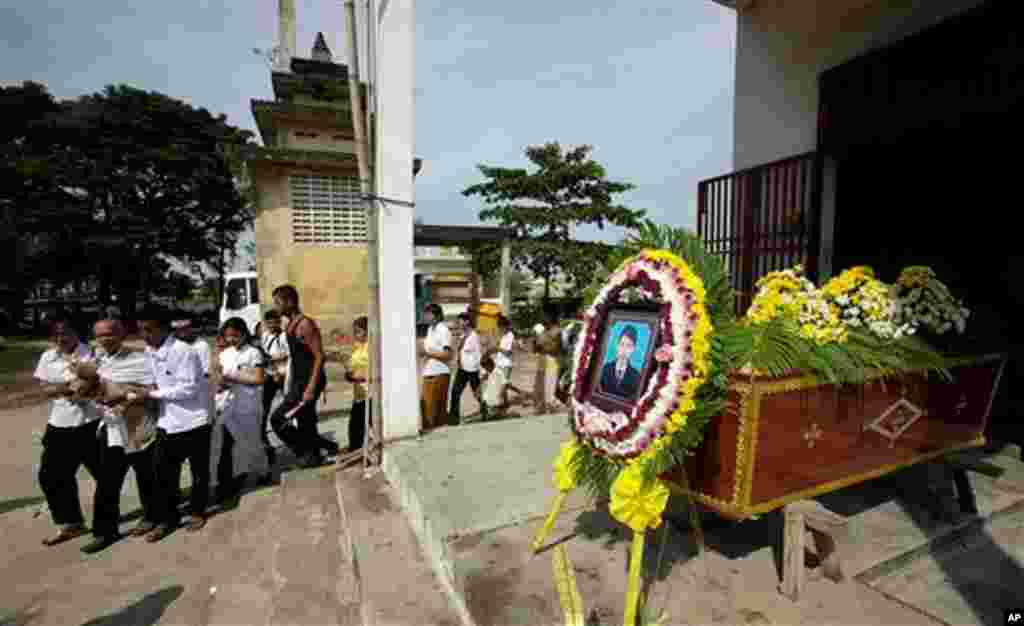Bun Oun, second left, who lost his daughter in Monday's stampede, gets help during her cremation at Sombourmeas temple in Phnom Penh, Cambodia, Wednesday, Nov. 24, 2010. An official investigation into the holiday tragedy that saw more than 350 people kill