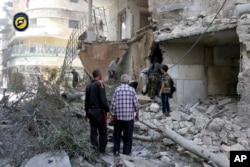 FILE - In this photo provided by the Syrian Civil Defense 'White Helmets,' rescue workers work the site of airstrikes in al-Mashhad neighborhood in the rebel-held part of eastern Aleppo, Sept. 21, 2016.