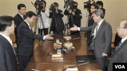 Ketua Delegasi Korsel Ryu In-chang (kanan) berjabat tangan dengan Ketua Delagasi Korut Yoon Yong -gun sebelum pertemuan, Selasa (29/3).
