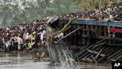 Warga desa Buraburi menarik bangkai perahu yang terbelah dari sungai Brahmaputra (1/5). Regu penyelamat dan penyelam telah menemukan sedikitnya 100 korban musibah tersebut, dan selebihnya masih dinyatakan hilang.