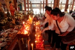 FILE - Local residents light candles during a ceremony to celebrate Pchum Ben, or Ancestors' Day at Krang Thnung Buddhist pagoda on the outskirts of Phnom Penh, Cambodia, Monday, Sept. 28, 2015.