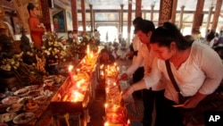 Local residents light candles during a ceremony to celebrate Pchum Ben, or Ancestors' Day at Krang Thnung Buddhist pagoda on the outskirts of Phnom Penh, Cambodia, Monday, Sept. 28, 2015. The traditional 15-day festival, which commemorates the spirits of the dead, began on Monday. (AP Photo/Heng Sinith)
