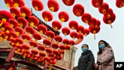 Women wearing face masks to help curb the spread of the coronavirus walk under red lanterns hanging along an alley near the Houhai Lake in celebration of the Lunar New Year in Beijing, Thursday, Feb. 11, 2021.