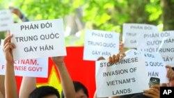 """越南人在河內中國大使館前示威,手持標語:""""制止中國侵佔越南土地"""""""
