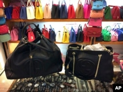 FILE - Counterfeit branded bags appear on display in a room hidden from the public area of a popular shopping mall in Beijing, China, March 11, 2015.