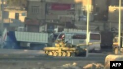 An image grab taken from a video uploaded on YouTube on August 22, 2012 allegedly shows a Syrian army tank deploying the the Nahr Aishe neighborhood of Damascus, August 22, 2012.